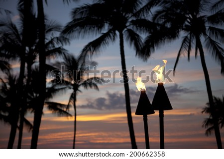 Flaming Tiki Lamps At Sunset - stock photo