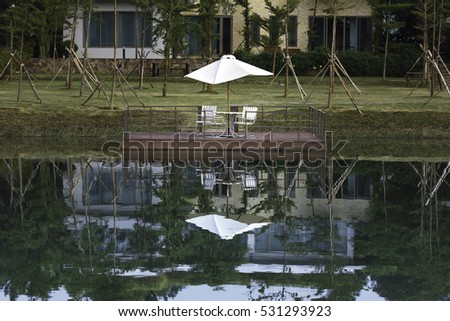 Flamingo Dai Lai, Vinh Phuc province, Vietnam - October 13, 2016 : lone wooden chairs sitting on the dock with a lake and cottages across