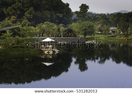 Flamingo Dai Lai, Vinh Phuc province, Vietnam - October 12, 2016 : table and chairs on wooden pier on shore of lake in summer landscape at Flamingo resort Dai Lai, Vietnam