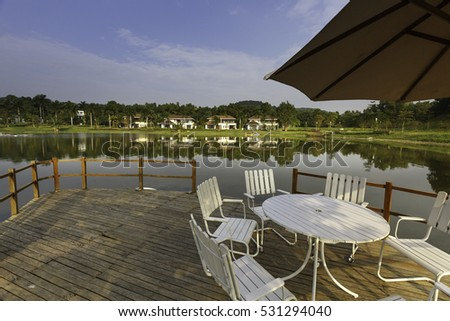 Flamingo Dai Lai, Vinh Phuc province, Vietnam - October 13, 2016 : table and chairs on wooden pier on shore of lake in summer landscape at Flamingo resort Dai Lai, Vietnam