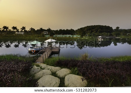 Flamingo Dai Lai, Vinh Phuc province, Vietnam - October 13, 2016 : walking path by stones to the pier on lake in Flamingo resort with dramatic sky at Flamingo Dai Lai resort of Vinh Phuc Province