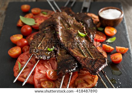 Flank steak on skewers with tomato salad - stock photo