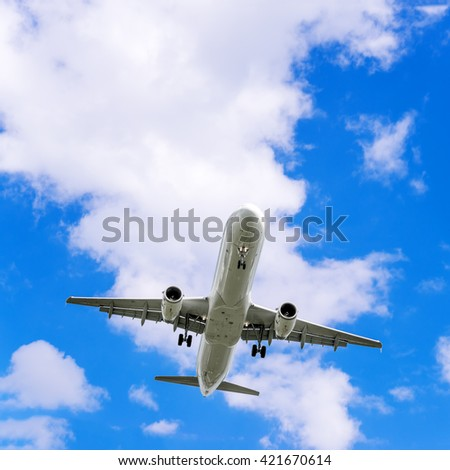 Flapping plane on a background of blue sky and white clouds.  Airliner. Bottom view.