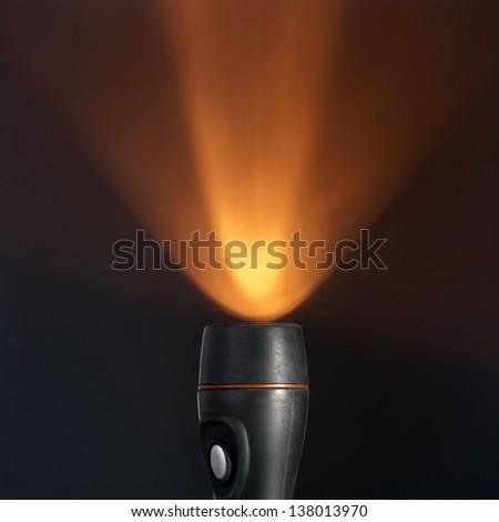 flashlight beam on dark background with copy space - stock photo