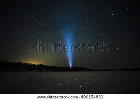 flashlight is shining up to the sky in the middle of the lake during the night - stock photo