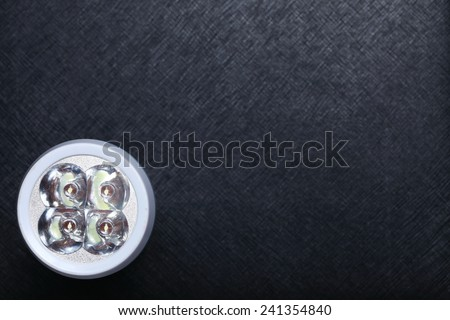 Flashlight LED type focusing on the head and reflection part an  put on black color leather surface background represent the light bulb technology - stock photo