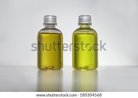 flask and small bottle with yellow hair shampoo