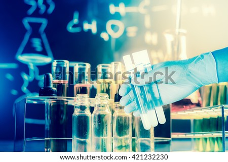 Flask in scientist hand with lab equipment background - stock photo