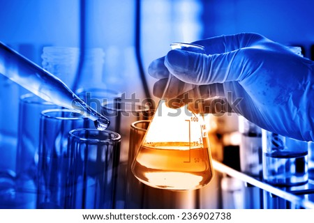 Flask in scientist hand with lab glassware background  - stock photo
