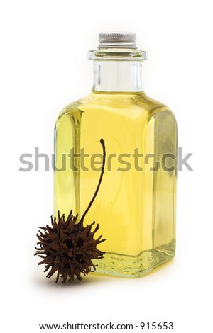 Flask of oil with sweetgum fruit on white background