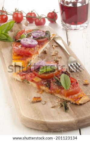 flat bread pizza with tomato, onion and basil on a wooden board - stock photo