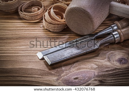 Flat chisels curled shavings wooden hammer on wood board construction concept.