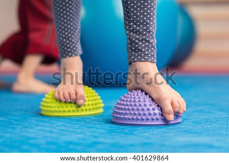 Flat feet correction exercise - Girl walking over spiked half balance massage balls - stock photo