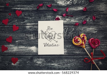 "Flat lay. A letter paper for Valentine's day with a gentle Love message ""Be my Valentine"" with paper red hearts,  sweets  Lollipop on Vintage black texture table."
