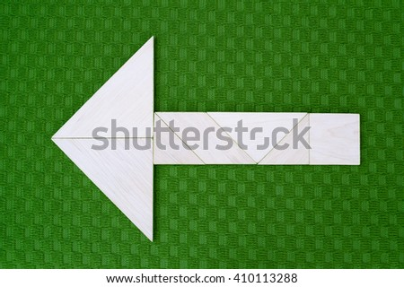 Flat lay - arrow showing direction made of wooden tangram pieces. Unicolor background made of green fabric texture. Vignetting. - stock photo