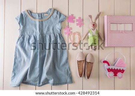 Flat lay children clothing and accessories on wooden background - stock photo