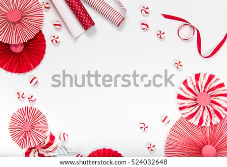 Flat Lay Christmas or Party Background with Candy, Decorations, and Wrapping Paper in Red and White. Room for Text in Middle.