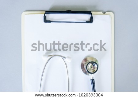 Flat lay design of stethoscope and blank clipboard pad with for medical concept. Top view.