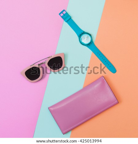 Flat lay fashion set:  mint blue watch, sunglasses and pink purse on pastel blue, pink and rose quartz colored backgrounds. Top view. - stock photo