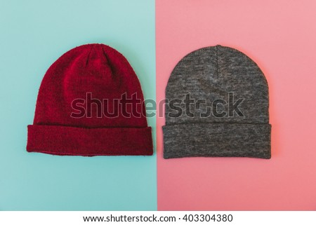 Flat lay fashion set: red and grey caps on pastel colored background - stock photo