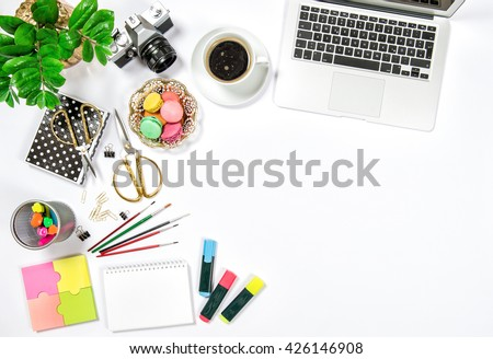Flat lay. Feminine office desk workplace. Coffee, cookies, photo camera, laptop computer and green plant on white table background. Top view. Flat lay - stock photo