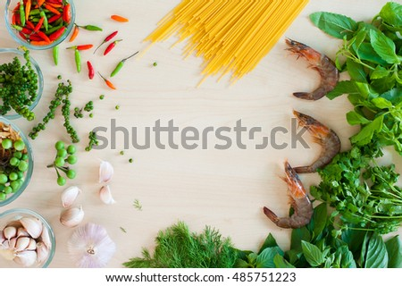 Flat lay fresh shrimp in bowl with mock up popular Thai herbal for food and spaghetti on wood table