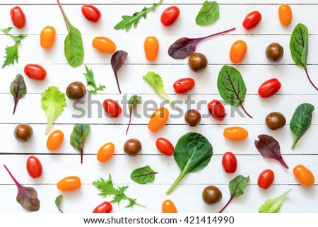 Flat lay healthy food ingredients. Top view food. Cherry tomatoes and salad leaves on white wooden background. Pizza ingredients - stock photo