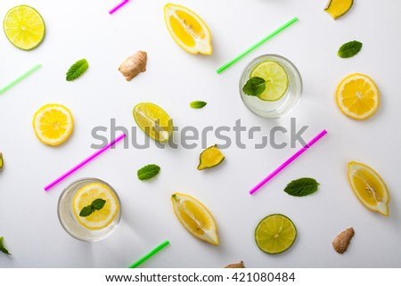 Flat lay ingredients for homemade lemonade. Lemon, lime, ginger and mint for refresh water lay in white background. - stock photo