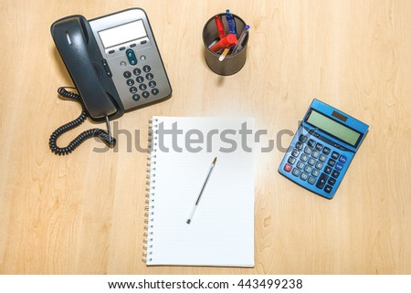 Flat lay of a business finance desk with accessories: a notepad, a calculator, penholder and a desktop telephone. Blank white paper for copy space