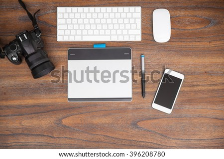Flat lay of a keyboard, digital camera, pen tablet and a smartphone on a wooden desk as a photographer's workspace - stock photo