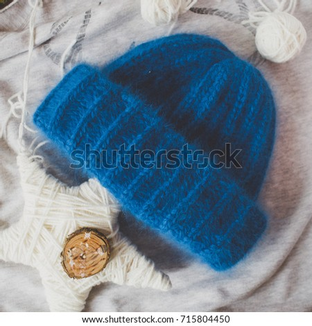 Flat lay of female fashion accessories and navy hat on textile background