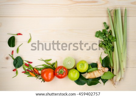 Flat lay of fresh Thai Tom Yum very delicious and famous dish's ingredients on wooden background composing of lemon grass, cilantro, galangal, kaffir lime leaves, limes, tomatoes, spicy bird peppers