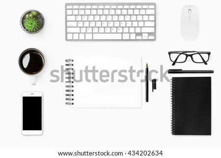 Flat lay of modern office table with blank notebook page in the middle with computer gadgets and office supplies around it. Top view. - stock photo