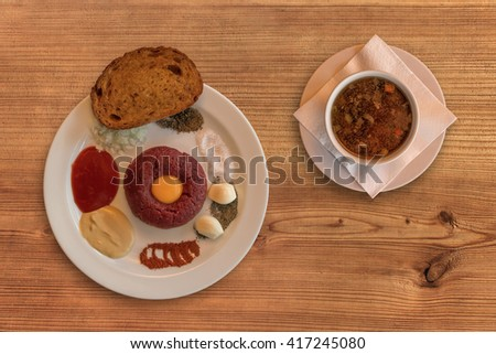 Flat lay of raw beef. Steak tartare. Steak tartare on rustic wooden table with a beef broth. Raw beef meat, salt, pepper, onion, caraway, mustard, tomato pyre, egg, garlic, toast or fried bread. - stock photo
