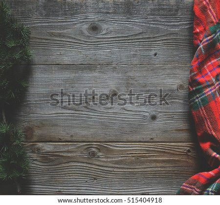 Flat lay of scarf with Christmas tartan texture and branch of tree on wooden background with space in middle - Christmas or New Year background