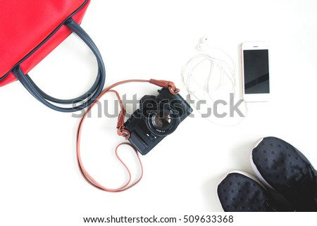 Flat lay of travel concept with camera, sneakers, mobile phone and shoulder bag on white background