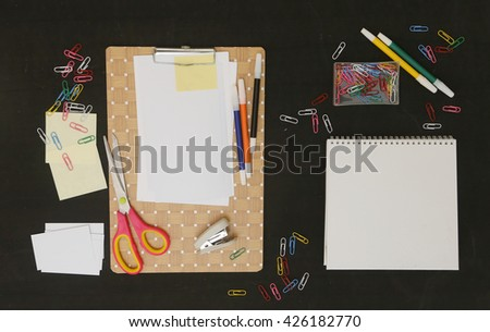 Flat lay photo of office desk with papers and lots of stationery objects