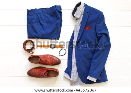 Flat lay set of classic men`s clothes such as blue suit, brown shoes, belt, watches and bracelet on white wooden background. Top view.