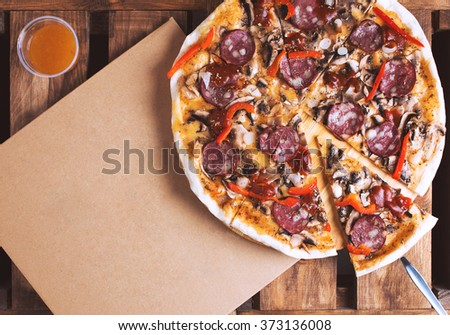 Flat lay shot of delicious italian pizza with meat and vegetables and cardboard delivery box. Pizza delivery service. - stock photo