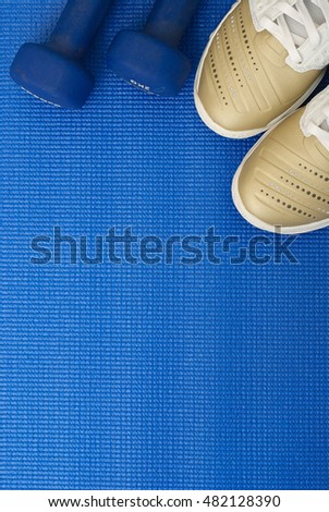 Flat lay shot of Sport equipment on yoga mat. Equipment for jogging, yoga, stretching, pilates