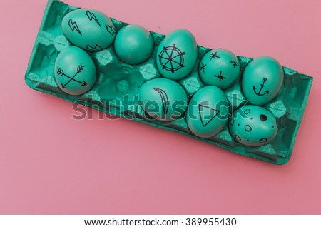 Flat lay stylish set: green hipster colored Easter eggs with marker inscriptions