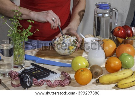 flat lay, Vegetarian meal, young girl preparing a healthy breakfast, fruit salad or muesli with yogurt. A healthy lifestyle, proper nutrition. Fresh fruits us a wooden table, Glassware. closeup - stock photo