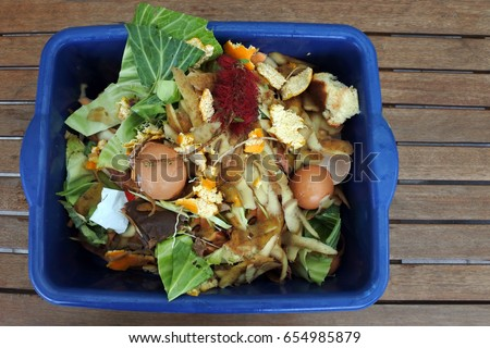 Flat lay view of container full of domestic food waste, ready to be composted in the home garden. Food recycling and environment concept. copy space
