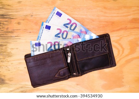Flat lay - wallet with Euro banknotes on wooden desk