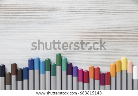 Flat layer of colored pencils of the Steel Shells Lie On a light wooden table in the form of a graph. Close Up. Creative ideas, creativity and early learning. Copy space for your text