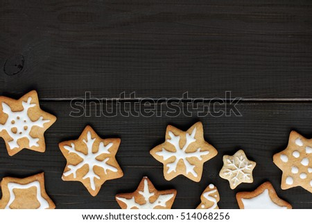 flat layout of the cookies in the form of stars and snowflakes on dark wooden surface top view / delicious festive Star fall