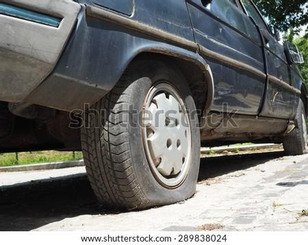 Flat rear tire on car - stock photo