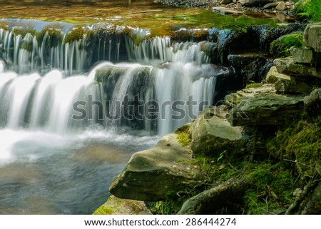 Flat rock ledge and a shallow clean clear brook with water cascading over moss covered stones - stock photo
