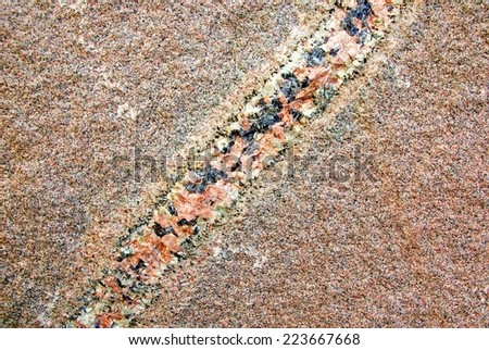Flat rock of red granite stone with a natural diagonal stripe.