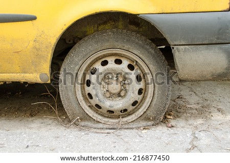 Flat tire of old yellow car on the parking - stock photo